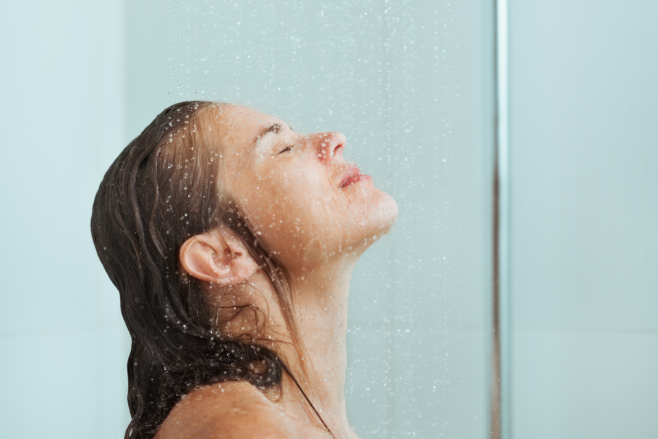 Woman in shower eyes closed